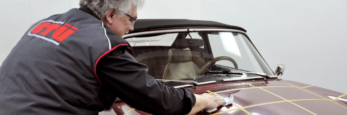 Mann im Kittel steht schräg neben Auto und trägt Politur auf