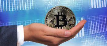 In der rechten Hand hält eine Hand eine Bitcoin Münze.