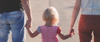 Kleines Kind zwischen seinen Eltern hält die Hände.