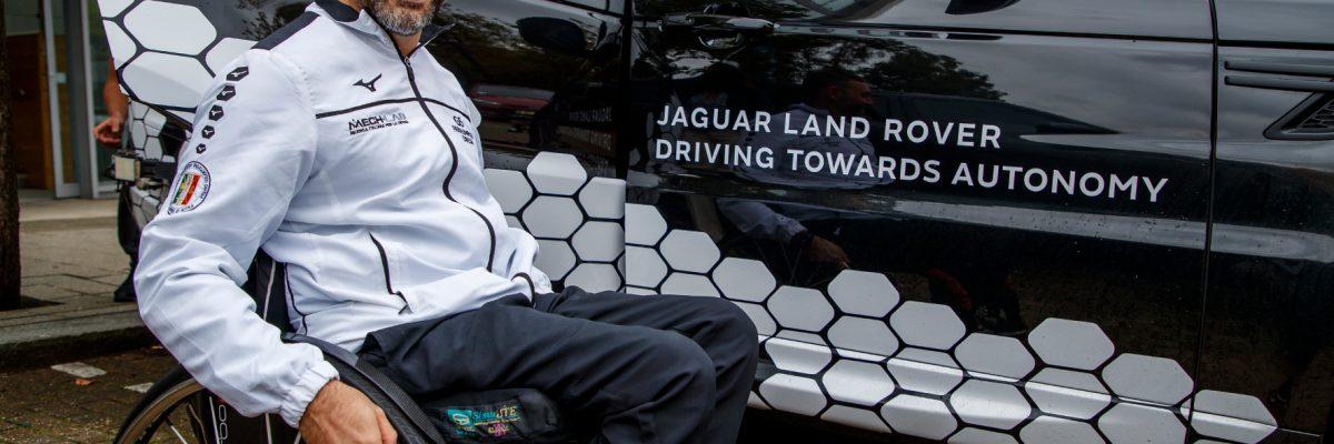 Mann lacht und sitzt im Rollstuhl neben Jaguar Land Rover Driving Towards Fahrzeug