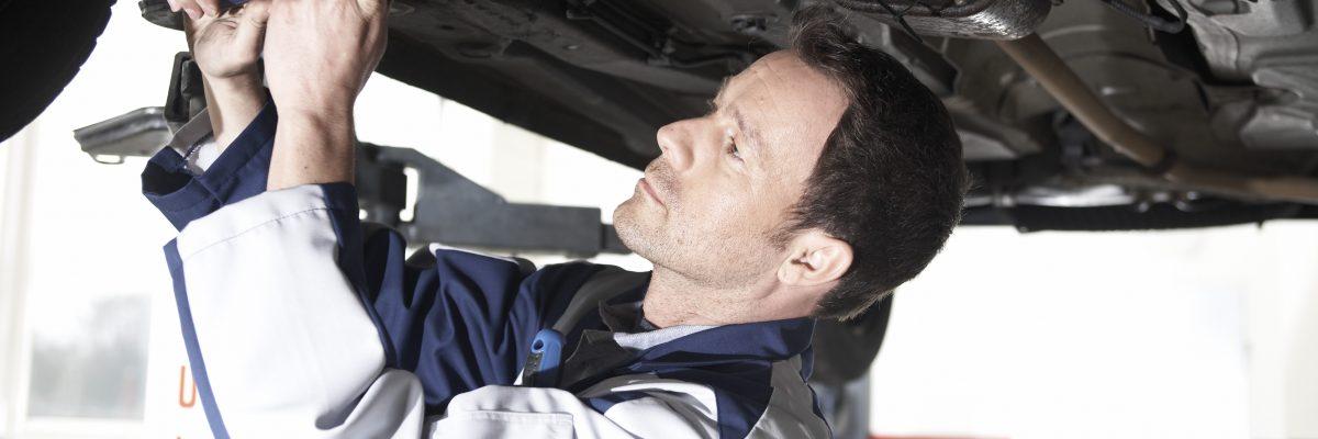 Man in Autowerkstatt schraubt
