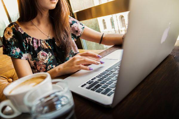 Junge Frau mit Kaffeetase vor Notebook