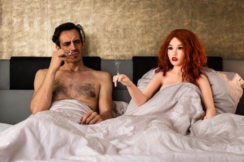 Mann mit Sexpuppe im Bett