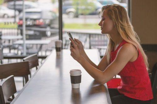 Junge Frau mit Smartphone an der Bar.