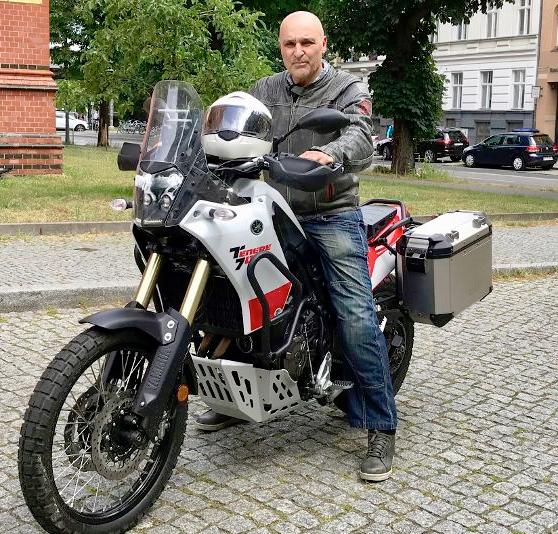 Motorradfahrer mit weißem Held auf dem Tank sitzt auf weißem Motorrad