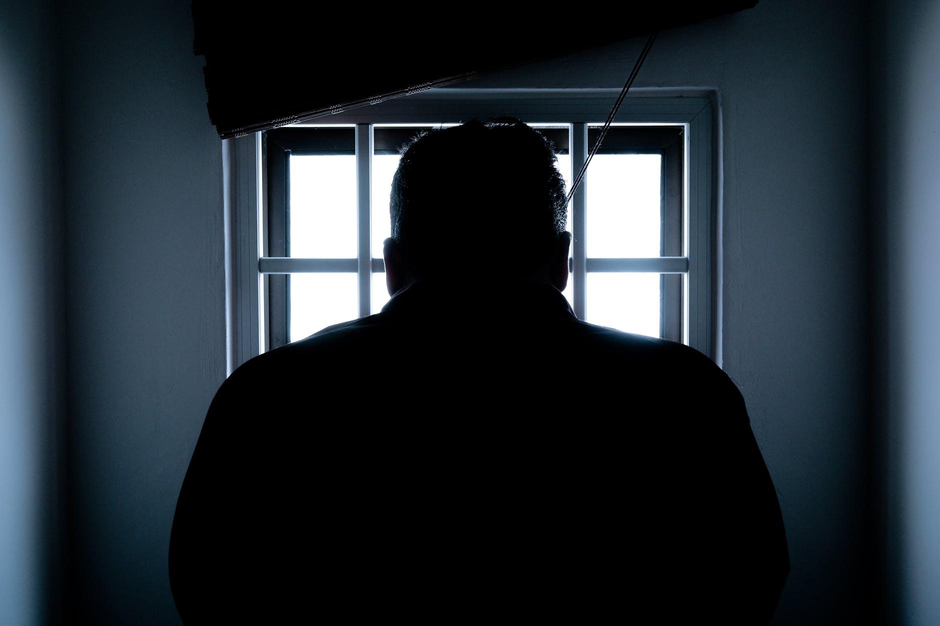 Gefangener in einer Zelle schaut durch Gitter zum Fenster raus.