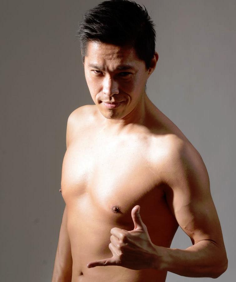 Mann mit freiem Oberkörper streckt Daumen und Finger.