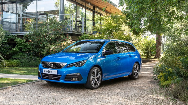 Blauer Peugeot 308 vor einem Haus im Hintergrund