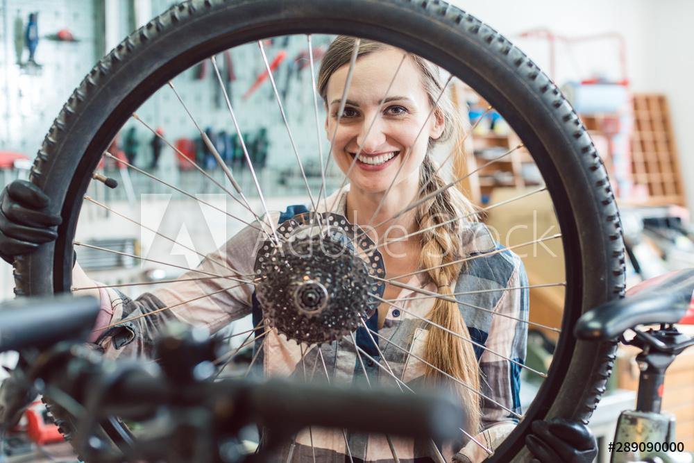 Fahrradmechanikerin schaut durch das Rad eines Fahrrads